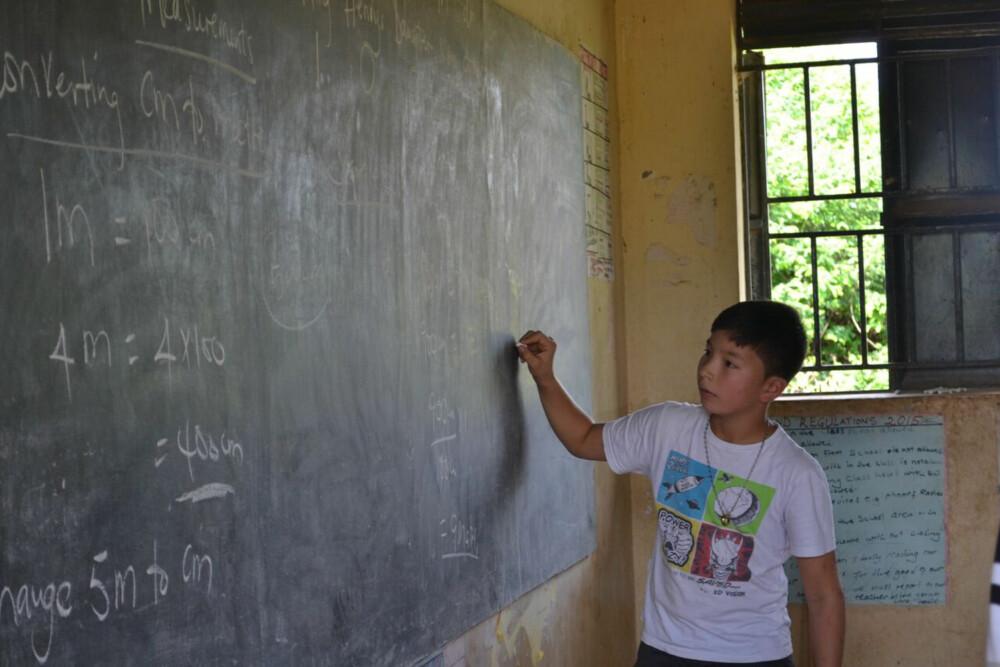 PÅ SKOLEN: Even Fredheim fikk oppleve hvordan skoledagen til barna i Uganda fortoner seg. Han fikk også prøve seg på tavla i en mattetime.