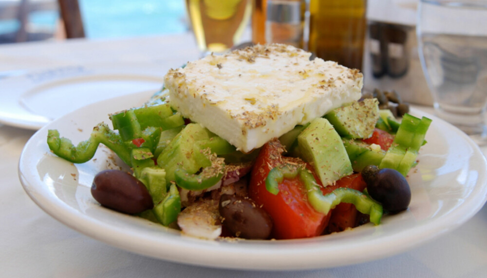 DET GODE GRESKE LIV: Gresk salat på bordet og stranden like ved. Dette er blant de store greske attraksjoner!