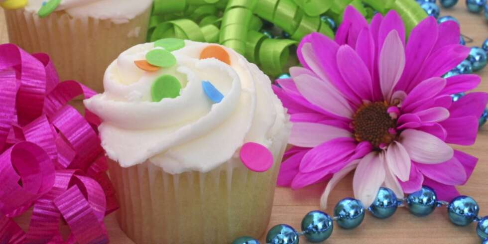 Cupcakes and Flower with Beads and Ribbon on Wooden Table
