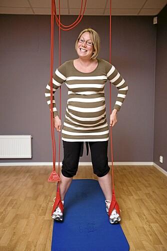 ØVELSE 1: Stående i slyngen fører Tone beina rolig fra hverandre og mot hverandre. Da aktiviseres kjernemuskulaturen i mage/rygg, samtidig som inn- og utside-muskulaturen av hoftene trenes. Øvelsen skal ha god effekt for bekkenpasienter.