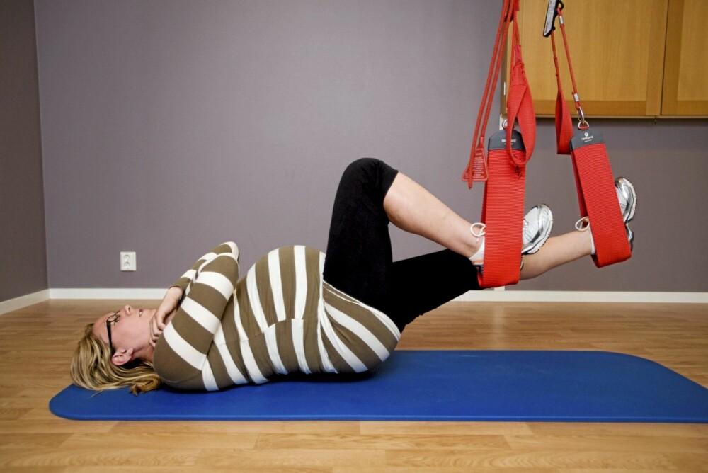 ØVELSE 3: Liggende på rygg med beina i slyngen, strammer Tone muskulaturen, før hun heiser bekkenet opp. Uten å synke sammen fører hun beina ut og sammen, løfter hælene mot rumpa og sykler. Så senker hun baken, og svinger beina fra side til side for å løse opp bekkenet.