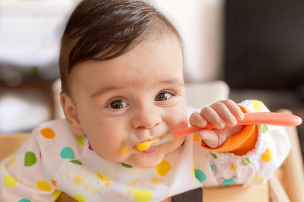 FRA MELK TIL FAST FØDE: La barnet bli trygg på å spise fast føde ved å få holde sin egen skje og spise selv.