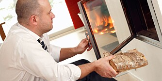 mid adult man in shirtsleeves making fire in fireplace in his living room after work