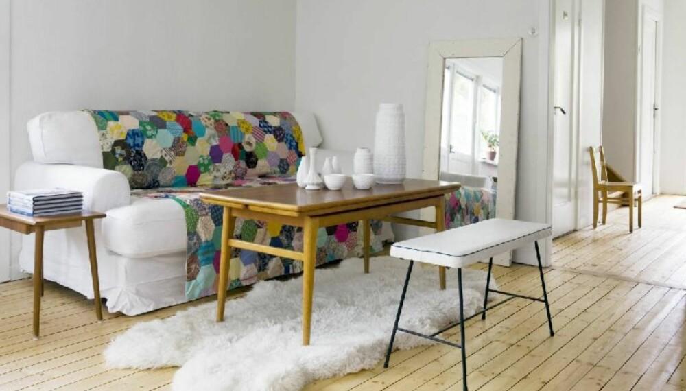 En spennende kombinasjon av retro og landlig stil fungerer utmerket i stua. Sofaen fra Ikea er frisket opp med et fargerikt patchworkteppe lagd av kluter som er sydd sammen. Mari bytter ut teppet innimellom - og skaper på den måten nye uttrykk i stua. Speilet sikrer ekstra romfølelse.