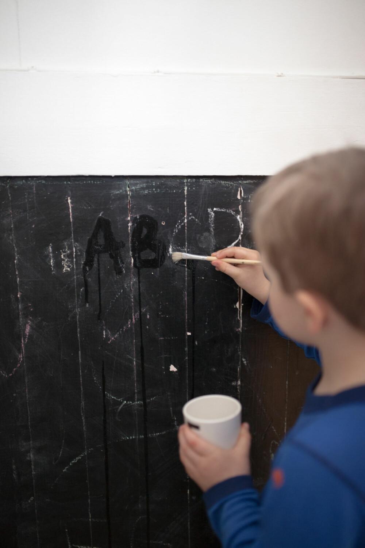 SKRIV PÅ TAVLE: Å male bort krittet på en tavle med vann kan hjelpe barna å forstå hvordan bokstavene skrives.