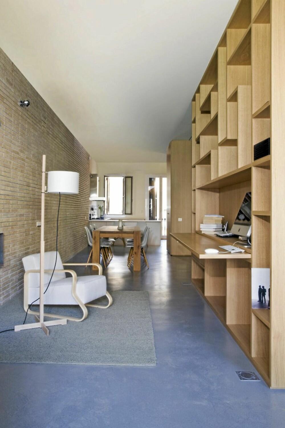 FLERFUNKSJONELL VEGG: : Den ene ytterveggen av trekuben fungerer som en hylle i stuen. Her har beboeren innstalert en skrivepult og hyllene gir godt med lagringsplass.
