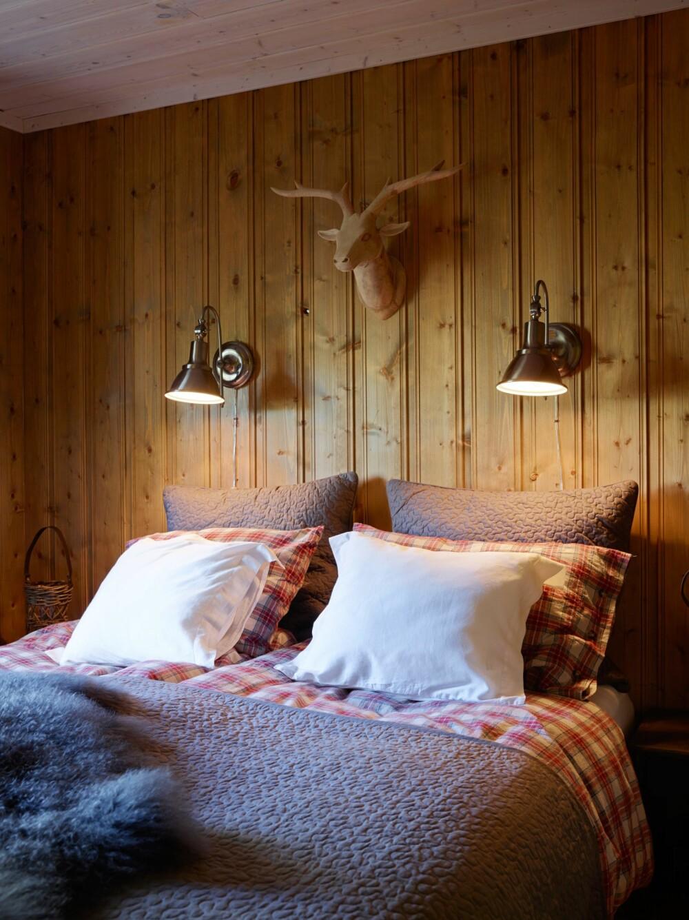 LUNT ROM: På hovedsoverommet er det en lun stemning. Lampene er fra Skeidar, dyrehodet og sengesett er fra Home and Cottage. Veggene her er beiset med Jotun interiørbeis i fargen 9041, Drivved, ett strøk.