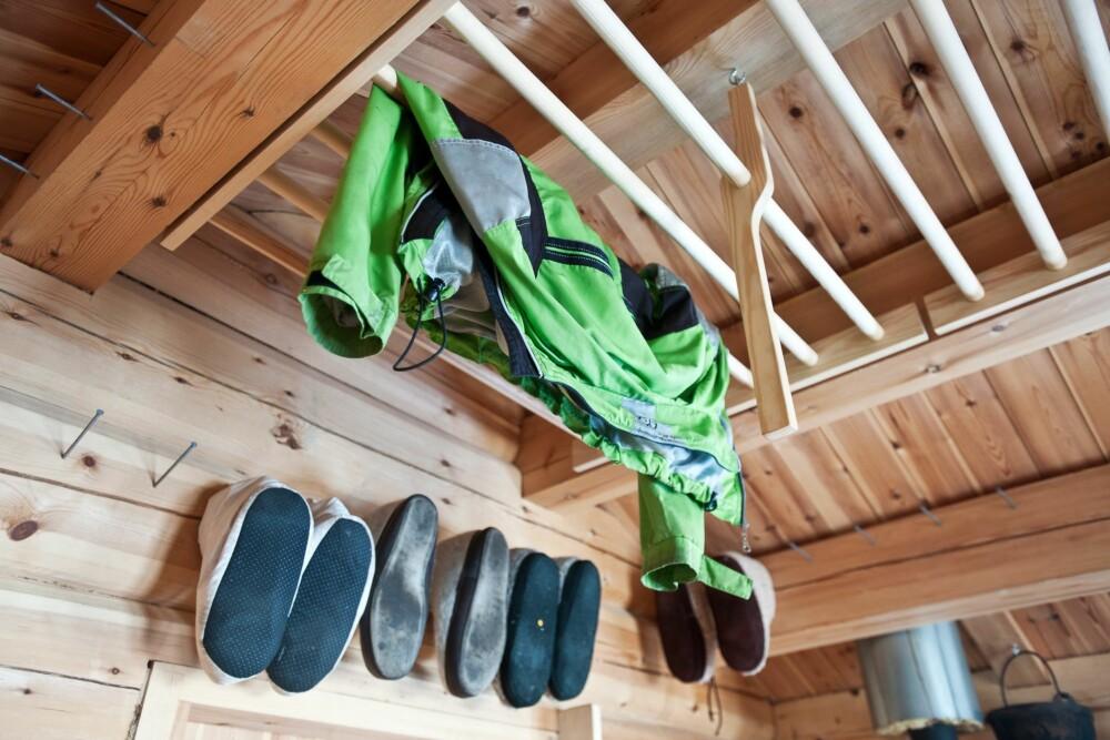 PLASSBESPARENDE: Dette heisbare tørkestativet i taket har arkitekt Bendik Manum fra Trondheim laget. Planken som henger ned fra taket er festet til en krok. Når den hektes av, senkes stativet ned, slik at du kan henge opp det du trenger av klær. Deretter løftes stativet opp igjen. Tøflene er hengt opp på veggen ved hjelp av store spikere. Dersom du skal gjøre dette; husk at de bør spikres litt over hodehøyde. Foto: Pasi Alto