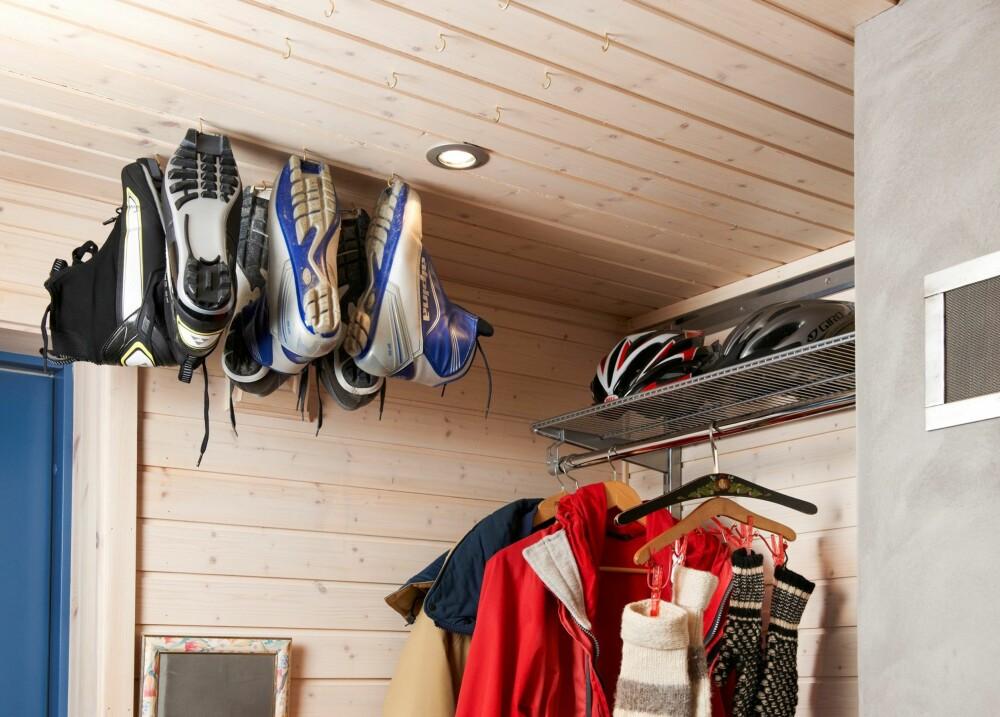HØYT HENGER DE: Plassmangel på hytta er et velkjent problem. I denne gangen har hytteeierne hengt opp skisko og støvler i små kroker. Tipset fikk de fra en kamerat som var lei av å snuble i støvler og sko i gangen, og fant ut at disse fint kan henges i enkle, små kroker. Varmen stiger som kjent opp til taket, så dermed tørker skoene også fortere. Dersom det er mulig, kan skoene henges over en varmekilde. Foto: Jan Larsen