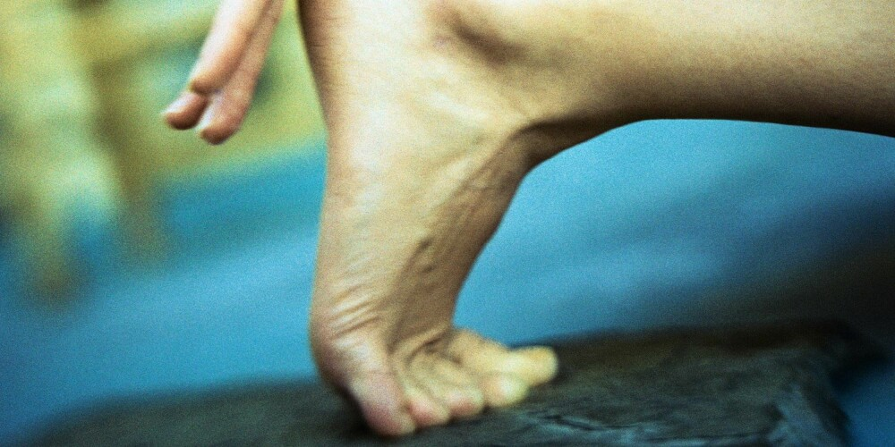Woman crouching, close-up of hand on heel