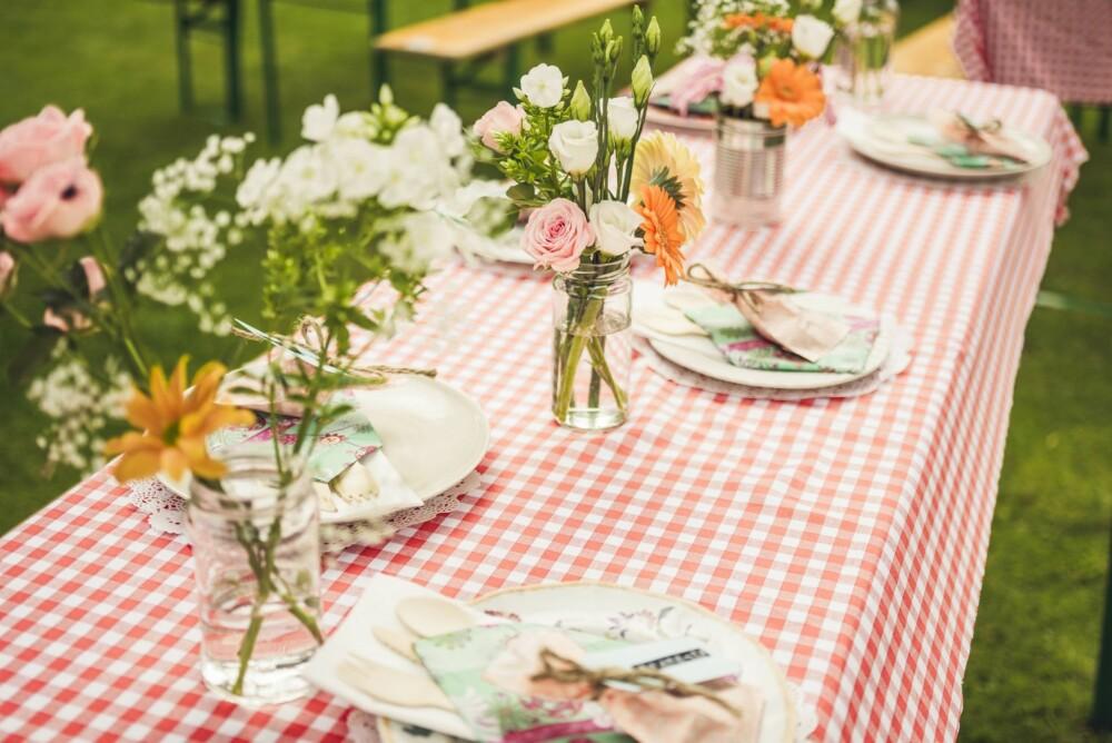 DEKKET TIL BORDS: Bordet var dekket av ulike typer asjetter som brudeparet hadde lånt, og blomstene stod i gamle syltetøyglass og hermetikkbokser.