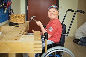 SNEKKER: Denne dagen har ikke Martin krefter til annet enn å bli kjørt i rullestol til hobbyrommet på sykehuset. Men å høvle og snekre henter frem livsglede hos guttungen.