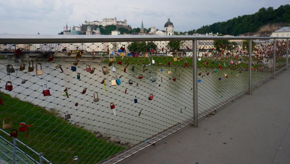 KJÆRLIGHET: På gjerdet til Makartsteg-brua over Salzach-elva henger utallige «kjærlighetshengelåser» med inngraveringer - dagens versjon av å skjære navn inn i trestammer.