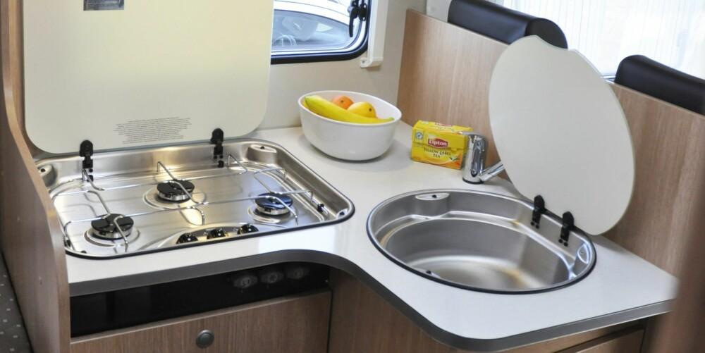ENKELT OG GREIT: Kjøkkenet er vinkelformet og ganske enkelt utstyrt. Doble 230 volts uttak, sprutvern og søppelbøtte i matskapet er det som stikker seg ut.