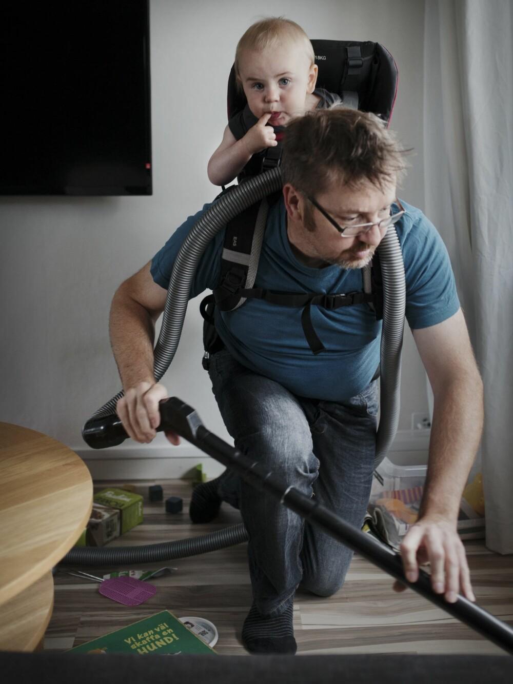 MULTITASKING: Ola Larsson støvsuger med sønnen Gustav på ryggen.