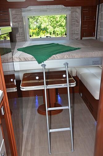 SENKESENG BAK: Sittegruppen bak har en seng hengende over seg, og den er klar på et blunk når det er natta.