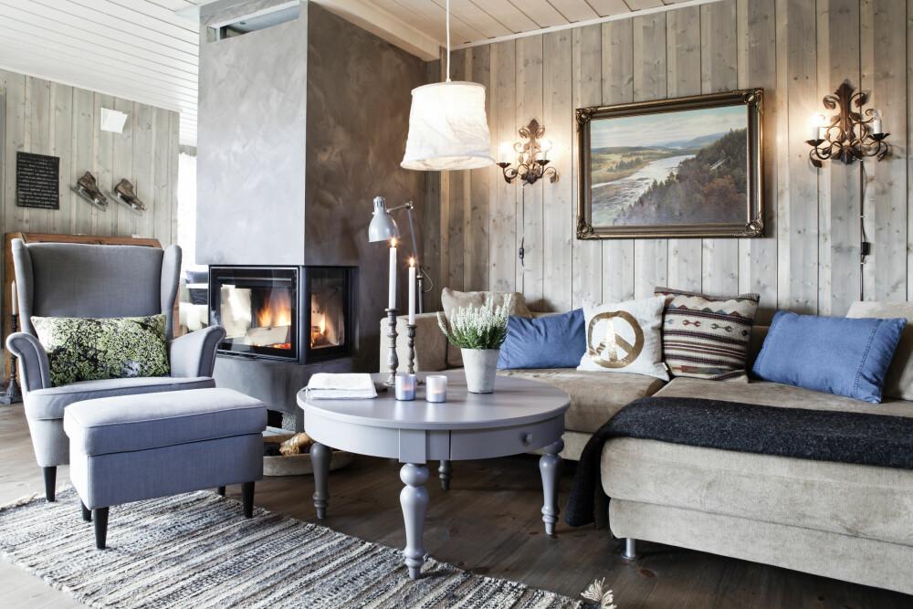 Peisinnsats fra Nordpeis og peiskappe malt med kalkmaling fra Pure & Original. Sofaen fra Habitat har en fin blanding puter som bringer sammen fargepaletten. Bildet har Elin arvet fra sine besteforeldre. Taklampen er fra Home&Cottage, stålampen fra Ikea og vegglampene fra Corniche. Lenestol og sofabord fra Ikea. FOTO: Linn Melum
