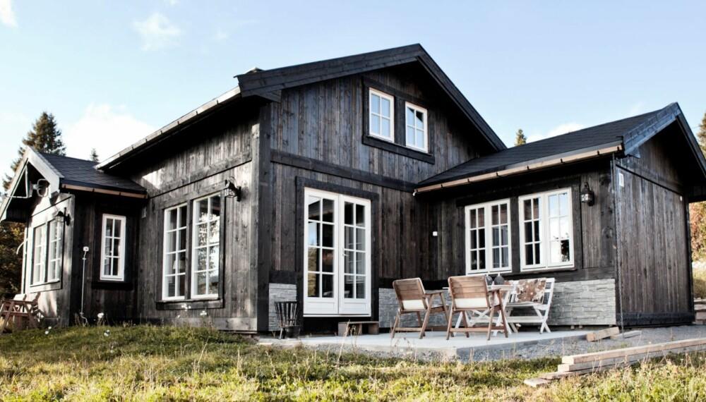 Hytta på Mylla, seks mil nord for Oslo, er sortbeiset med hvite vinduer. Enkelte veggpartier er kledd med skifer, som går igjen på uteplassen. På taket er det lagt sort takpapp. FOTO: Linn Melum