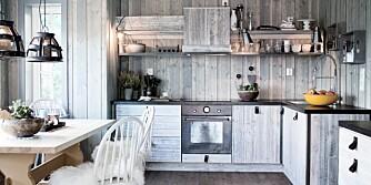 Kjøkkeninnredningen er fra Ikea med spesialbestilte fronter fra Drivved.no i hvitbeiset tre. En benkeplate i mørk laminat fra Ikea er fin kontrast. Veggene er malt med et lag Lady interiørbeis i fargen patinagrå, mens taket er holdt i lys grå og gulvet i Sjøsand. Alle harmonerer godt, og viser kjøkkenet til sin rett. Åpne hyller innredet med pene ting som er ofte i bruk. Klypelamper fra House Doctor. FOTO: Linn Melum