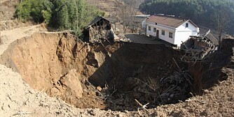 The debris of houses devastated by a subsidence is seen next to and inside the massive sinkhole in Pingxi village, Guangyuan city, southwest Chinas Sichuan province, 12 December 2013. A massive sinkhole in Pingxi village of Guangyuan city in southwest Chinas Sichuan province opened up around 00:40 a.m. after midnight on Thursday (12 December 2013) and had expanded into a crater measuring 60 by 40 meters around and 30 meters-deep within hours. The sinkhole has swallowed at least 12 buildings as of 6:30 p.m. and is expected to keep growing in size. Casualties in the subsidence were still unknown. - photographed: December 12, 2013