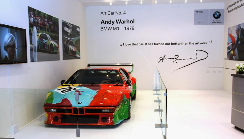 VERDT TITALLS MILLIONER: Rykter vil ha det til at denne Andy Warhol-dekorerte M1'en er en av de mest verdifulle bilene i BMWs bilsamling. Se det herlige sitatet fra Warhol selv på veggen bak.