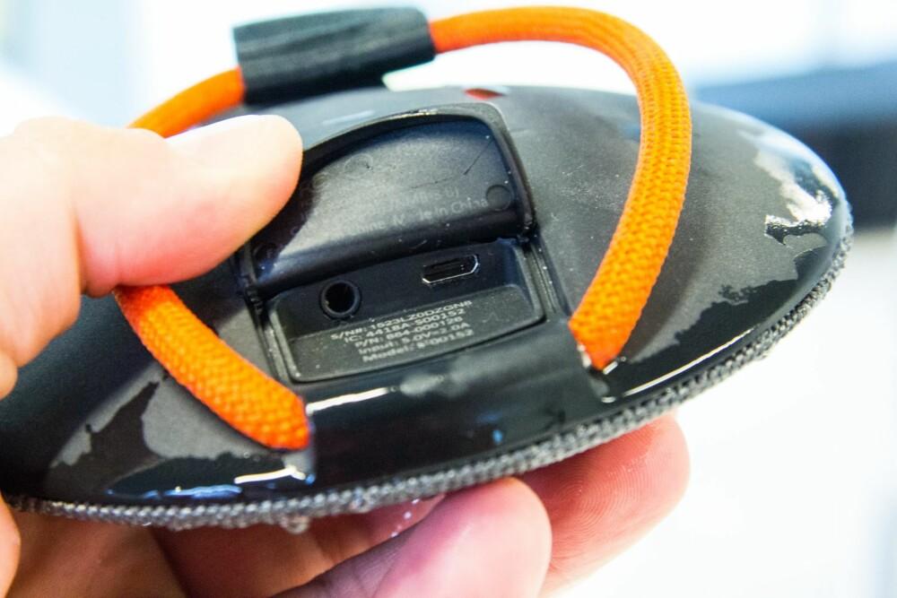 PORTER: Ladeinngang og inngang for hodetelefoner er gjemt bak et gummiert deksel. Den gummierte reimen kan løsnes på den ene siden, slik at høyttaleren kan henges opp eller festes til noe.