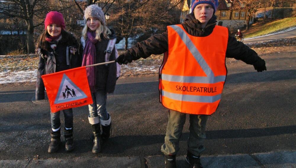 UENIGHET: Skolepatruljen samler ofte opp en gruppe elever ved å stå slik ved fotgjengerovergangen. Ifølge politiet kan du da kjøre. Trygg Trafikk og bymiljøetaten i Oslo sier derimot at bilister skal stanse. FOTO: Trygg Trafikk