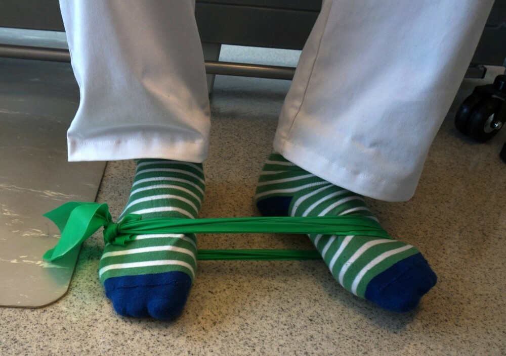 ØVELSE 5: Knyt sammen et gummibånd eller strikk og fest den rundt føttene. En fot er helt stille, mens den andre foten glir langs gulvet. Hælen står stille mens fremre delen av foten roterer utover langs bakken. Dette trener opp muskulaturen på utsiden av leggen som er viktig i forhold til problemer som sitter under fotbuen. 15 repetisjoner hver vei.