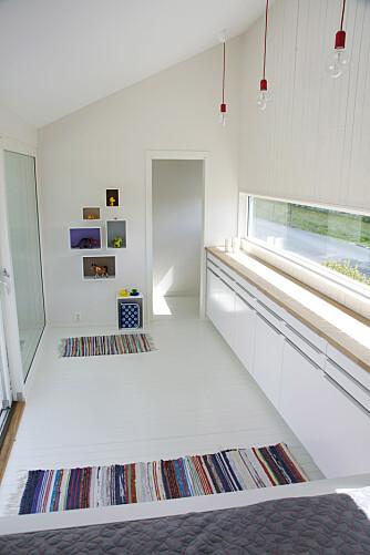 Inne er malt i samme hvitfarge som utenfor, så områdene henger sammen. Smart og praktisk innredning med sengehjørne i ene enden, og et lite rom som skal bli toalett i andre enden. Mellomrommet har en smal kjøkkenbenk av skapmoduler fra Ikea og benkeplate fra Obs.