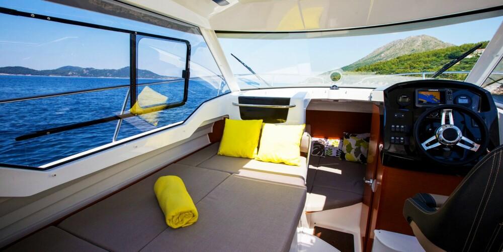 INGEN OVERRASKELSER: Cockpit har førerplass og lite pantry på høyre side og en kompakt sittegruppe med bord på venstre. Hovedkøya ligger nede under dekk, der det også er plass til et lite toalettrom på høyre side.