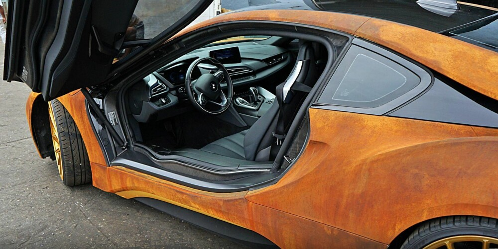 TO VERDENER: Supermoderne på innsiden, rustikk på utsiden. Etter en runde hos MetroWrapz vekker Mahones BMW i8 uten tvil oppsikt. FOTO: MetroWrapz