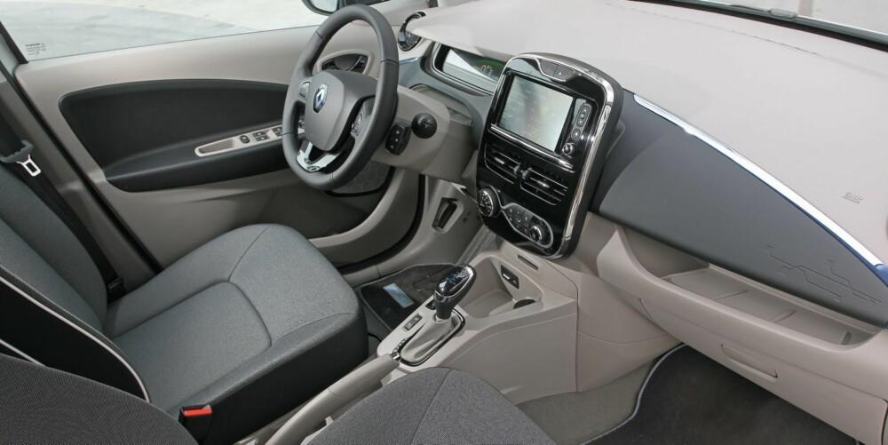 INNVENDIG: Sittestillingen i Renault Zoe er det man kan kalle halvhøy. Materialkvaliteten i interiøret er typisk for rimelige småbiler. På skjermen i midten kan du finne veien til nærmeste ladestasjon og sjekke om du kjører økonomisk. FOTO: Petter Handeland