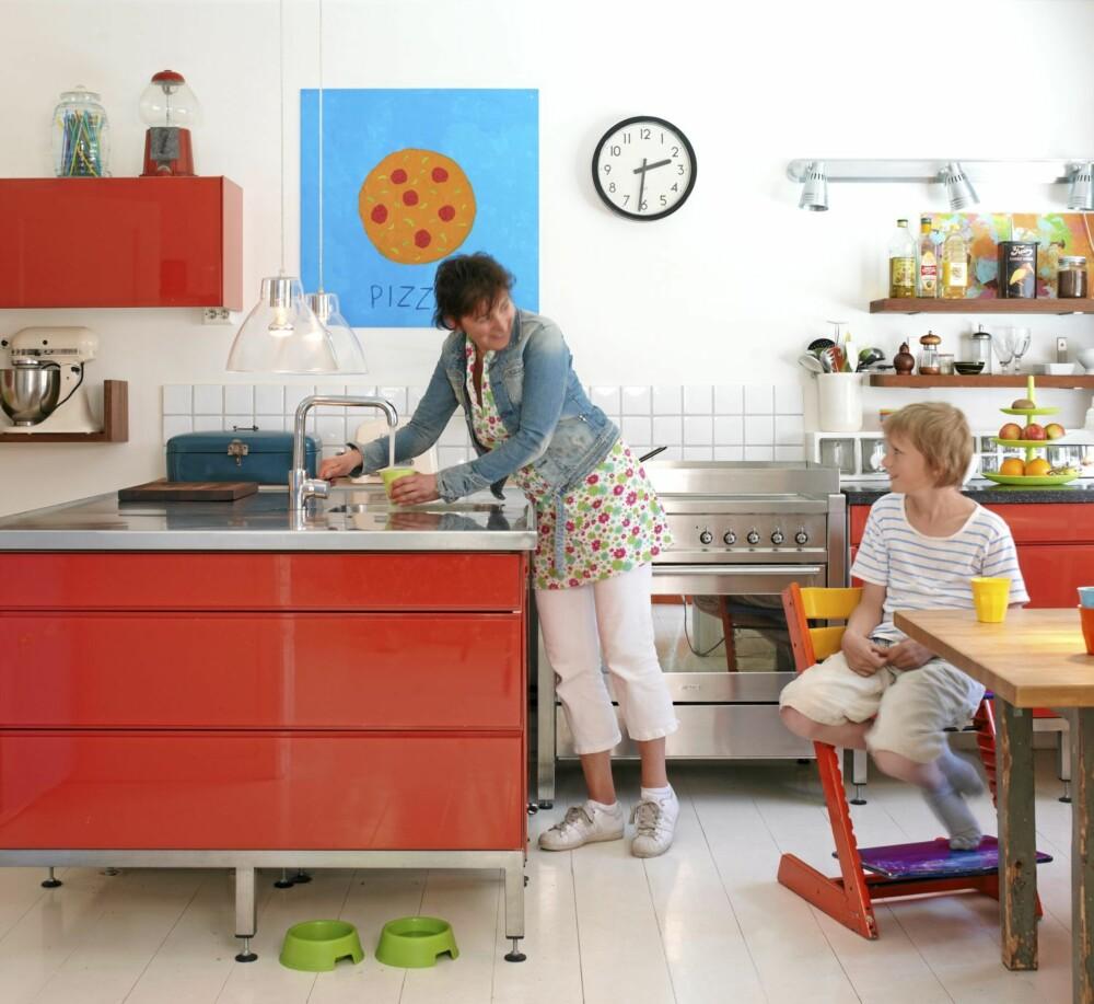 RØDT OG RØFT: Kari Nysæther og sønnen Mikkel på kjøkkenet. Innredningen er fra Multiform, den tikkende veggklokken er fra en gammel togstasjon.