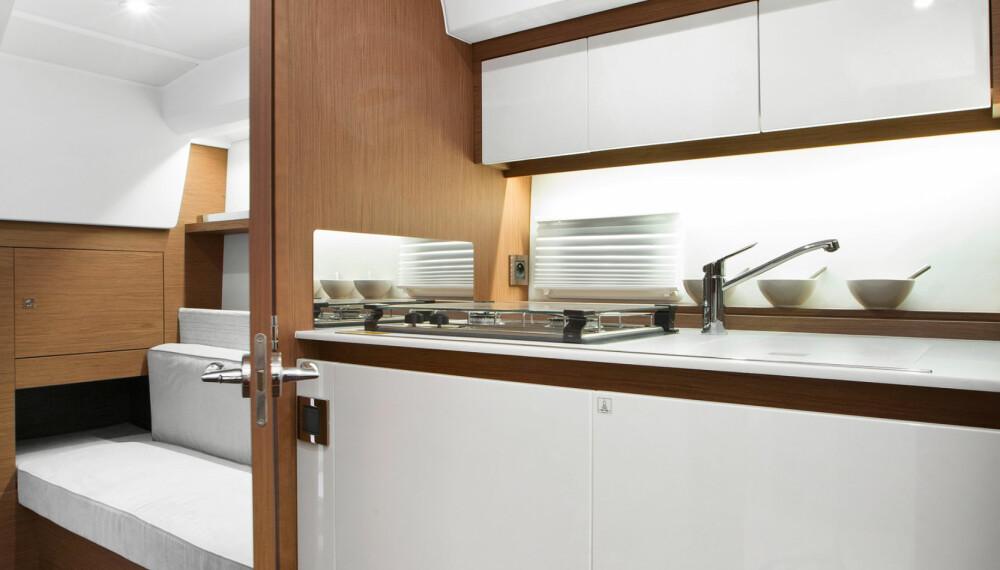 BYSSE: Lyse materialer gjør det hyggelig å lage mat, selv under dekk. I bakkant inngangen til akterkabinen (Foto: Jeanneau).
