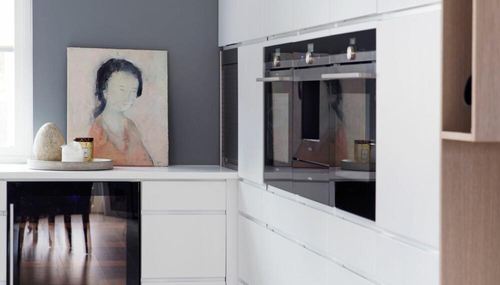 STRAMT KJØKKEN: Den hvite innredningen fra Kvik er kledd med en ramme i tre. Det gir det stramme kjøkkenet varme, samtidig som det får et unikt uttrykk. I tillegg er det ekstra oppbevaringsplass i hyller i rammen. En møbelsnekker har stått for løsningen. Komfyren og kaffemaskinen i svart er spennende mot det hvite. Et maleri gir kjøkkenet personlighet. Så enkelt kan det gjøres (FOTO: Yvonne Wilhelmsen/STYLING: Tone Kroken).