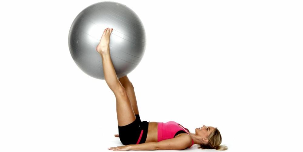 BEINLØFT: Hold beina strakt opp i lufta med ballen mellom anklene.