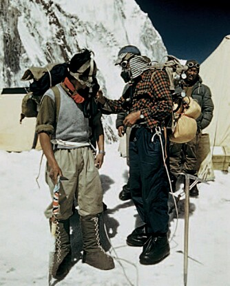 Norgay til venstre og Hillary i camp 4, fire dager før de står på Everest. De er klare for action. Hillary sjekker oksygenutstyret til Norgay, som har montert flagg på isøksa si.