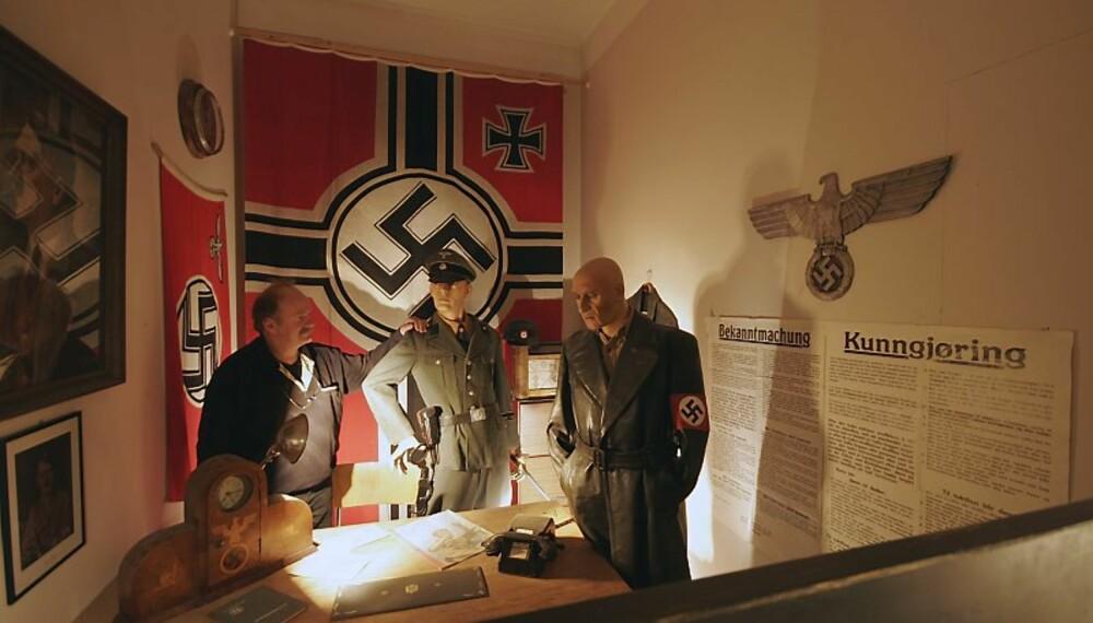 NATURTRO:Det er noe skummelt over det naturtro Gestaporommet med det svære naziflagget, nazisymbolet og plakaten med sin Bekanntmachung. Du føler at her har dødsdommene sittet løst. En av personene på bildet hører ikke naturlig hjemme i dette tidsbildet. Ser du hvem?