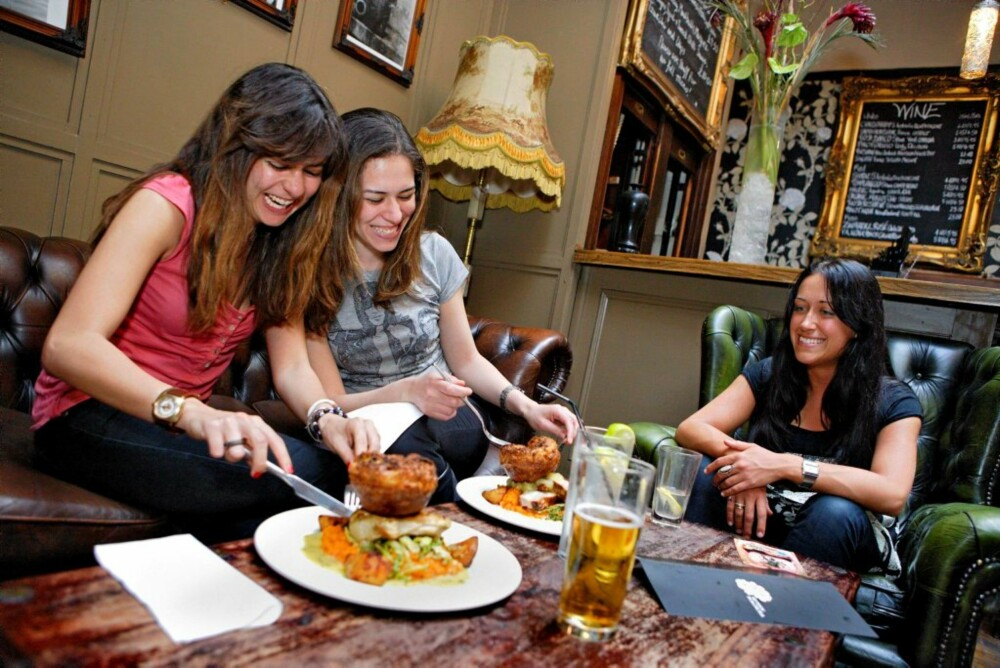 """SØNDAGSENGLER: Rana Fahmy (til venstre) og Shahira Kamal nyter sin """"Sunday roast"""" på gastropuben Queen Boadicea. Veganervenninnen Lisa Stockton må nøye seg med å se på."""