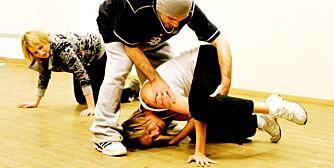 Kristina får hjelp til å komme seg opp i et klassisk breakdance-løft, og Hanne Mette følger nysgjerrig med.