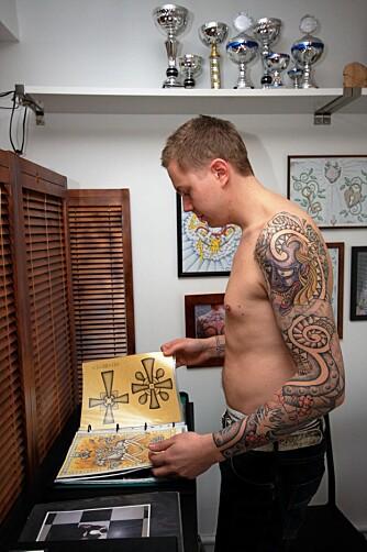 VALGETS KVAL: Denne kare, Lasse, ser ut ti lå ha bestemt seg for å holde på en stund, og har blar i bilder av andre tatoveringer for å få inspirasjon.