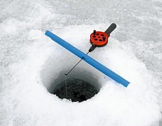 SMART: Det er viktig å sikre pilkestikker og snører mot å bli dratt gjennom hullet når ørreten drar i vei. Her blir stikka på isen!