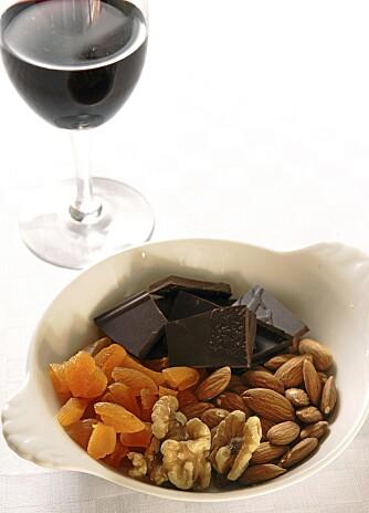 HJERTEGODT: I begrensede mengder er faktisk disse godsakene svært hjertevennlige: Mørk sjokolade (minst 70% kakao), nøtter (særlig valnøtter) og et glass rødvin.