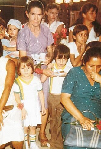 HARD BARNDOM: Maria vokste opp i et barnehjem der hun hadde mange plikter. Her står Maria med stripet sokker og kjole foran fostermor.