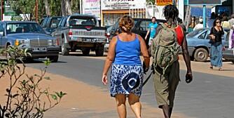 HÅND I HÅND: En middelaldrende hvit kvinne går hånd i hånd med en ung gambier i byen Kololi. På gaten her er sexturismen åpenlys.