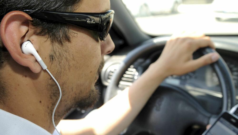 KJØRER MED SKYLAPPER PÅ: Mannen på bildet fikler med en iPhone. Men det er ikke nødvendigvis iPhonen som utgjør en fare i trafikken, det er solbrillene hans - som får en slags skylappfunksjon med de brede brillestengene. Dermed kan han ikke oppdage bevegelse i vidsynet.
