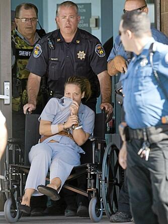 Ikke mye glamour igjen hos Lee Grace etter at hun ble beskutt av politiet. Her trilles hun ut av sykehuset - på vei til varetekt.