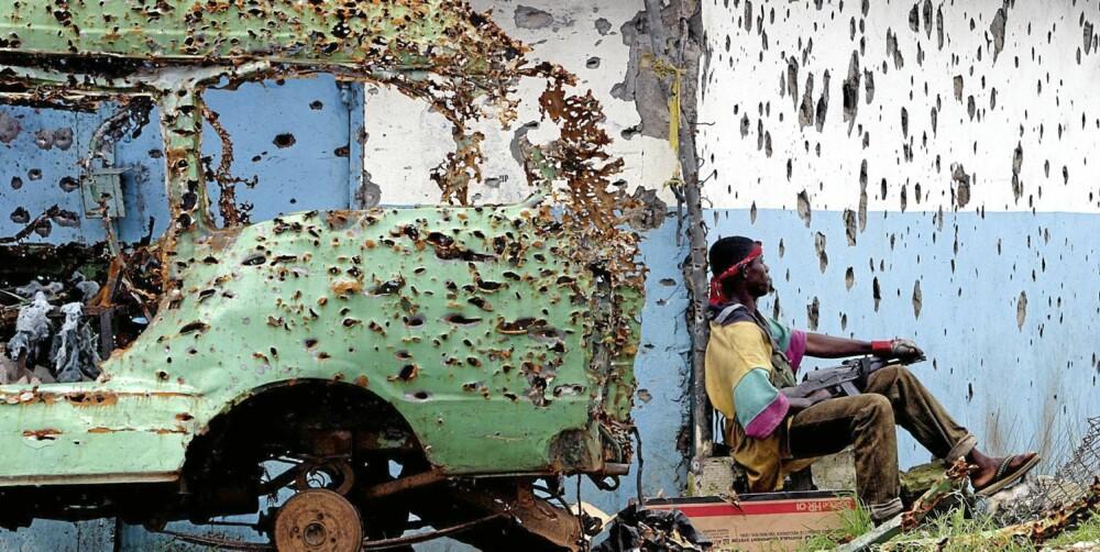 En opprørssoldat puster ut i et øyeblikks våpenhvile blant sønderskutte hus og kjøretøy, under borgerkrigen i Liberia i 2003.
