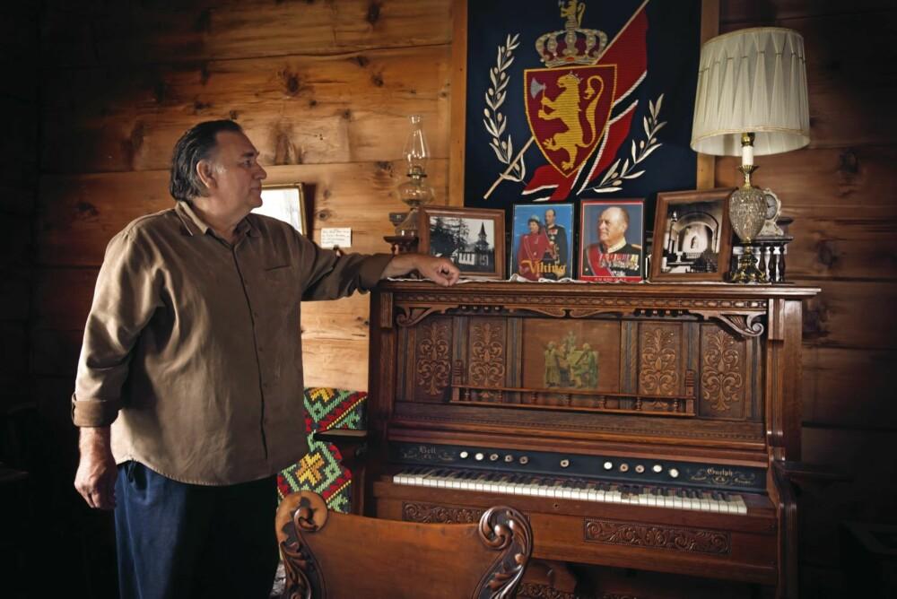 Peter Solhjell foran kongebilder og det norske flagget i det restaurerte hjemmet til den norske nybyggeren Andrew Svisdahl.