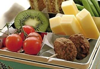 LYKKEN ER: En matboks med mange små rom kan bli den reneste skattkiste! Denne er fylt med grovbrød og hvitost kuttet i staver, en halv kiwi, en liten klase cherrytomater, to små kjøttkaker og en håndfull sukkererter. Bon appétit!